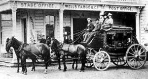 """Powóz Wells Fargo z woźnicą (""""King of the Road"""") oraz strażnikiem uzbrojonym w Winchester."""